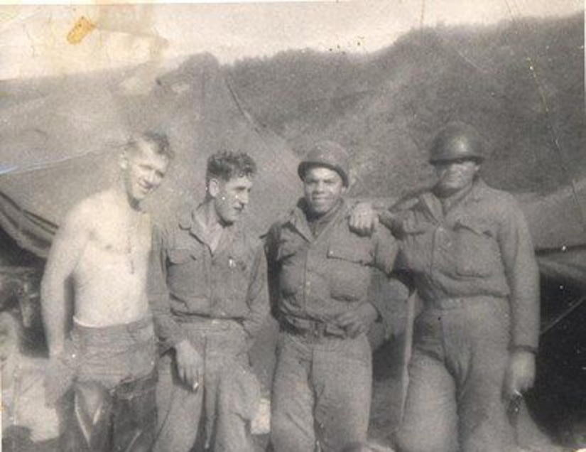 Four soldiers pose for a photo; mountains and tents are in the background.