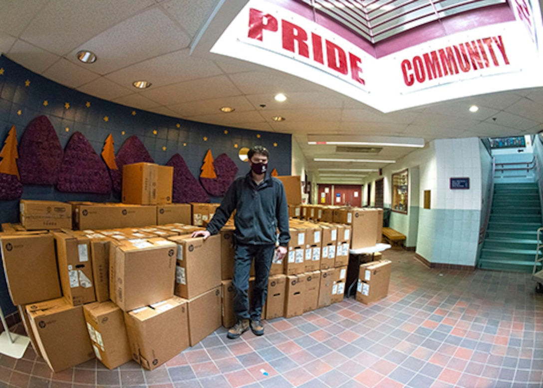 Steve Bourget stands with a stack of new computers in boxes.