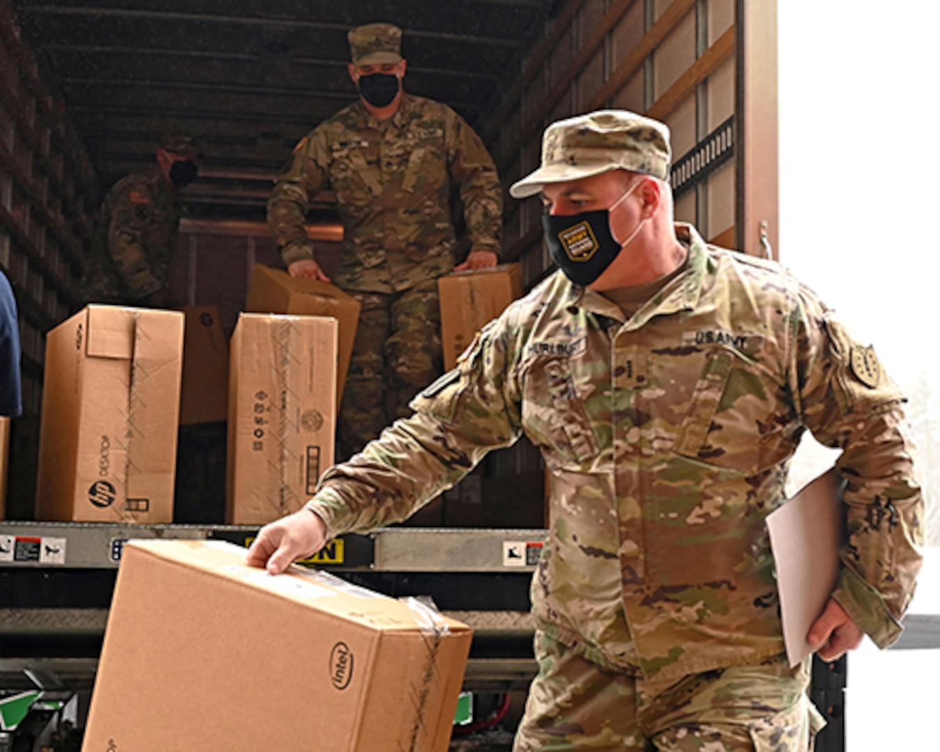 Soldiers in uniforms unload boxes from a truck with computers in them.