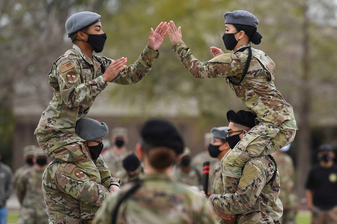 Two airmen sit on the shoulders of two other airmen while clapping hands.