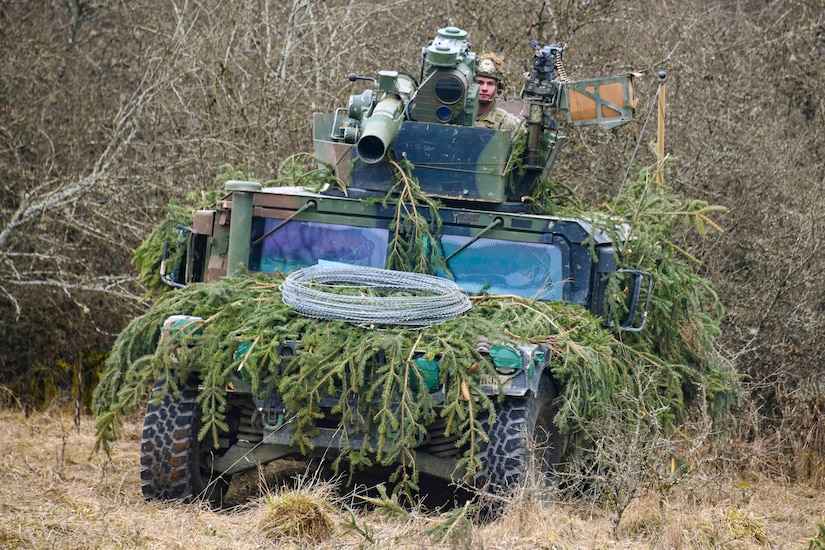A soldier travels in a military vehicle camouflaged by tree branches.