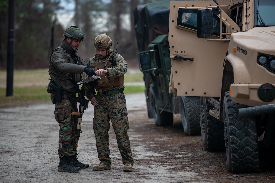 A Dutch Marine with 32nd Raiding Squadron, left, and U.S. Marine Corps Staff Sgt. Brady Parks, a native of Logan, Ohio, and a maintenance chief with 2d Reconnaissance Battalion (Recon Bn.), 2d Marine Division, discuss a scheme of maneuver during Exercise Caribbean Urban Warrior on Camp Lejeune, N.C., March 23, 2021. The exercise is a bilateral training evolution designed to increase global interoperability between 2d Recon Bn. and 32nd Raiding Squadron, Netherlands Marine Corps. (U.S. Marine Corps photo by Lance Cpl. Jacqueline Parsons)