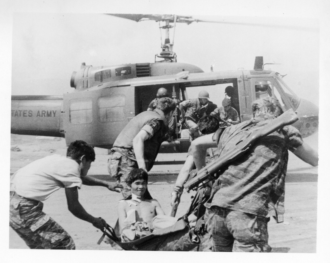 Soldiers carry a shirtless man on a stretcher to a helicopter.