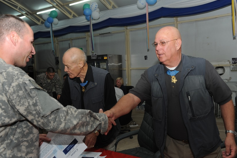 A soldier shakes hands with a man wearing a medal who's standing behind a table.