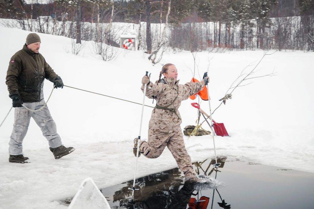 A service member holds a rope connected to a Marine who is jumping into freezing water surrounded by snow.