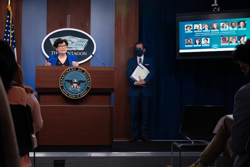 """A woman stands at a lectern. A man stands behind her to the left. On a television screen at the rear are the faces of multiple individuals. A sign on the lectern reads """"Department of Defense."""""""