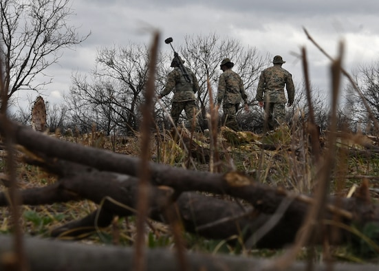 U.S. Marine Corps Tactical Signals Intelligence Operator course students from the Marine Corps Detachment, snake through brush and debris during an intelligence field exercise outside of the MCD dormitories on Goodfellow Air Force Base, Texas, March 22, 2021. The students operated in small teams, which were designed to optimize the training curriculum and simulated real-life scenarios. (U.S. Air Force photo by Senior Airman Abbey Rieves)