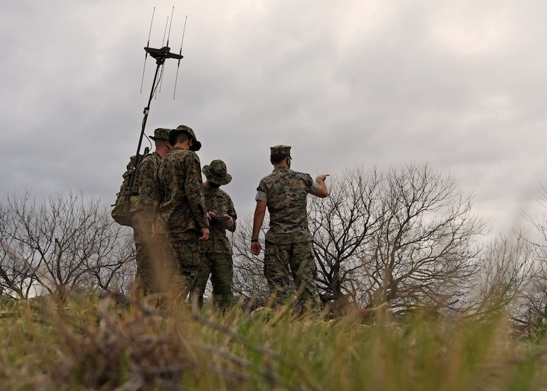 U.S. Marine Corps Gunnery Sgt. Zachary Fulk, Marine Corps Detachment Tactical Signals Intelligence Operator course instructor, offers insight and recommends new techniques for the TSOC students, who are locating an enemy signal emitter with their versatile radio observation and direction finder during a field exercise outside of the MCD dormitories on Goodfellow Air Force Base, Texas, March 22, 2021. Fulk and other MCD instructors were trained to challenge their students in order to promote educational attainment and expand warfighting readiness. (U.S. Air Force photo by Senior Airman Abbey Rieves)