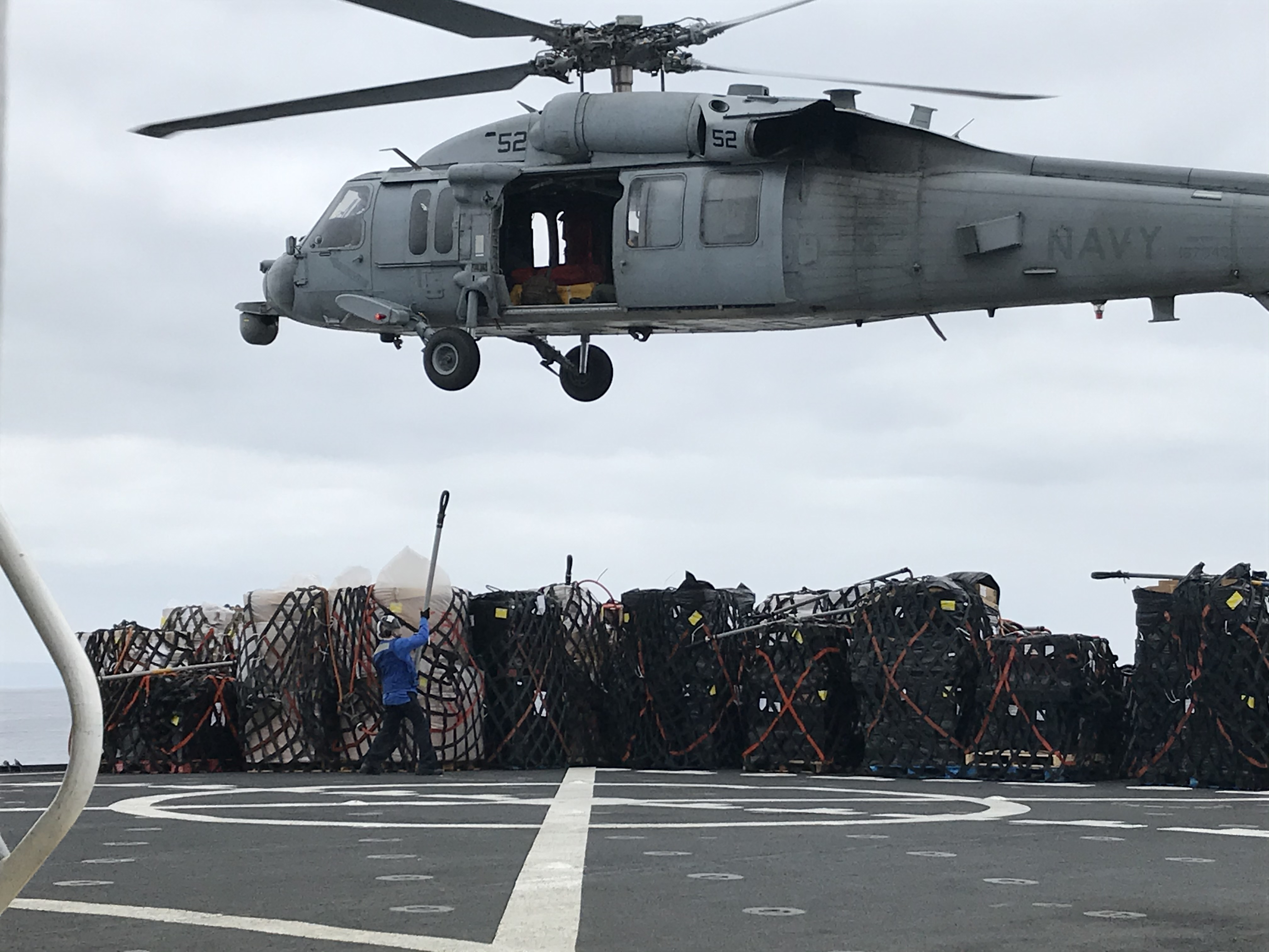 Military Sealift Command's Navy Cargo Afloat Rig Team personnel providing support during vertical replenishment operations.