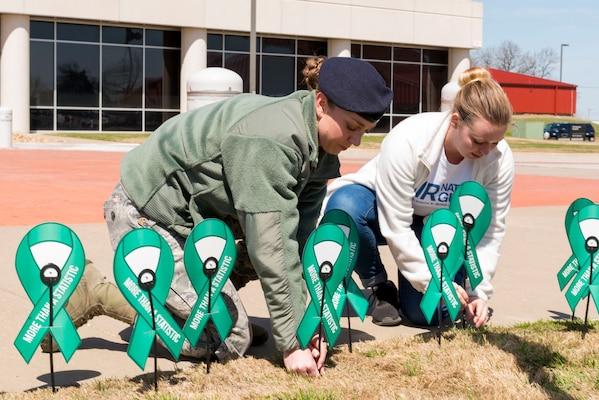 Airmen build a display of teal ribbons.