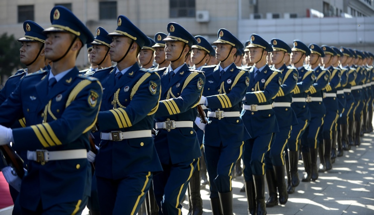 Chinese military service  members march in formation.
