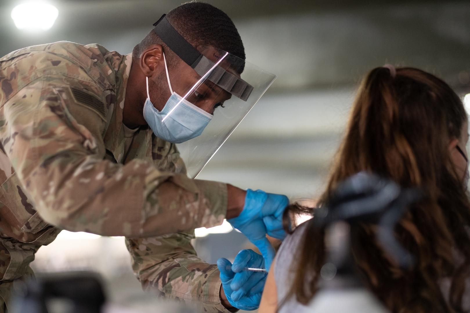 A U.S. Army combat medic administers a COVID vaccine.