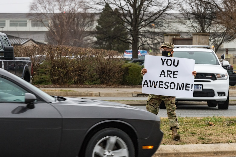 Lt. Col. Abner Valenzuela, 436th Airlift Wing head chaplain, holds a sign displaying a positive affirmation as vehicles pass through the main gate on Dover Air Force Base, Delaware, March 24, 2021. Valenzuela and other members of Team Dover held signs as vehicles approached and entered the base. (U.S. Air Force photo by Roland Balik)