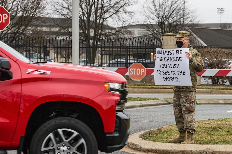 Capt. Jonathan Dawson, 436th Airlift Wing chaplain, holds a sign displaying a positive affirmation as vehicles pass through the main gate on Dover Air Force Base, Delaware, March 24, 2021. Dawson and other members of Team Dover held signs as personnel entered the base. (U.S. Air Force photo by Roland Balik)