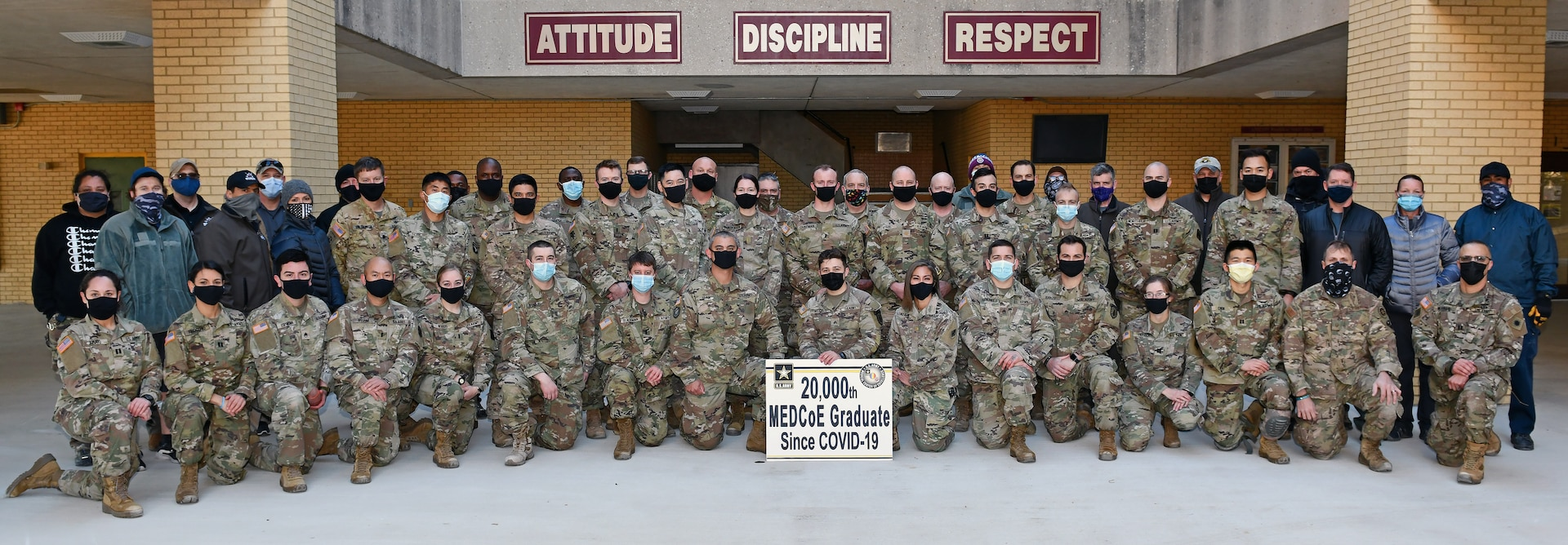 Sgt. Carter McCall (center) holds the 20,000th U.S. Army Medical Center of Excellence graduate since COVID-19 sign along with his classmates and course cadre.
