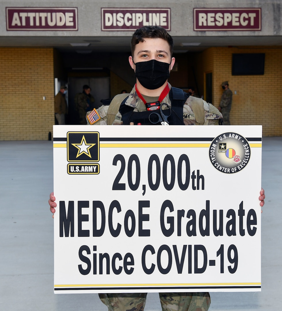 Sgt. Carter McCall holds a sign that signifies him as the 20,000th U.S. Army Medical Center of Excellence graduate since COVID-19.