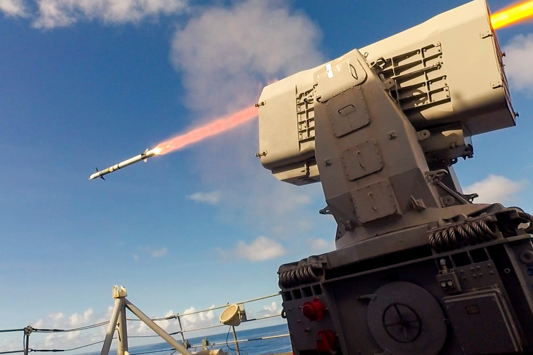 A ship fires a missile at sea.