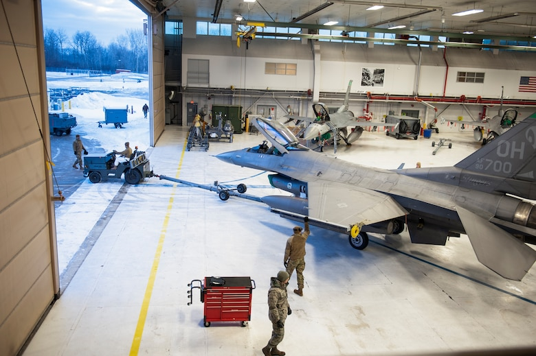 U.S. Air Force F-16 maintenance personnel, assigned to the Ohio National Guard's 180th Fighter Wing, begin to tow jets from the hangar, to the flightline, in preparation for early morning training sorties, Feb. 7, 2021.