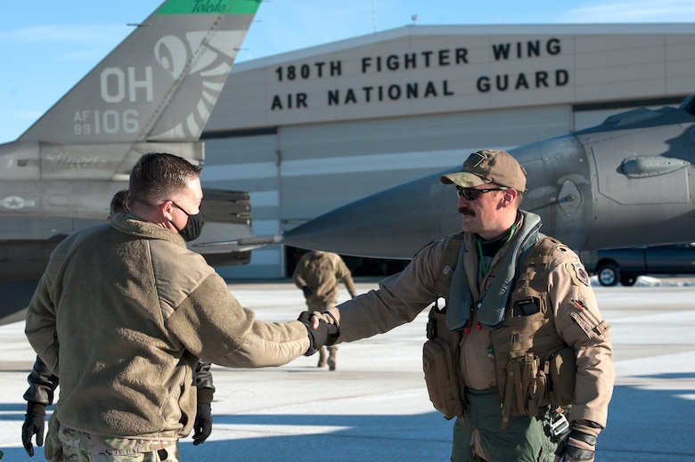 Ohio National Guard, Assistant Adjutant General-Air, Maj. Gen. James Camp, greets F-16 Fighting Falcon pilot, Lt. Col. Curt Voltz, assigned to the Ohio National Guard's 180th Fighter Wing after Voltz returned home from a three-month Aerospace Expeditionary Force deployment to Bagram Air Base, Afghanistan, Jan. 23, 2021.