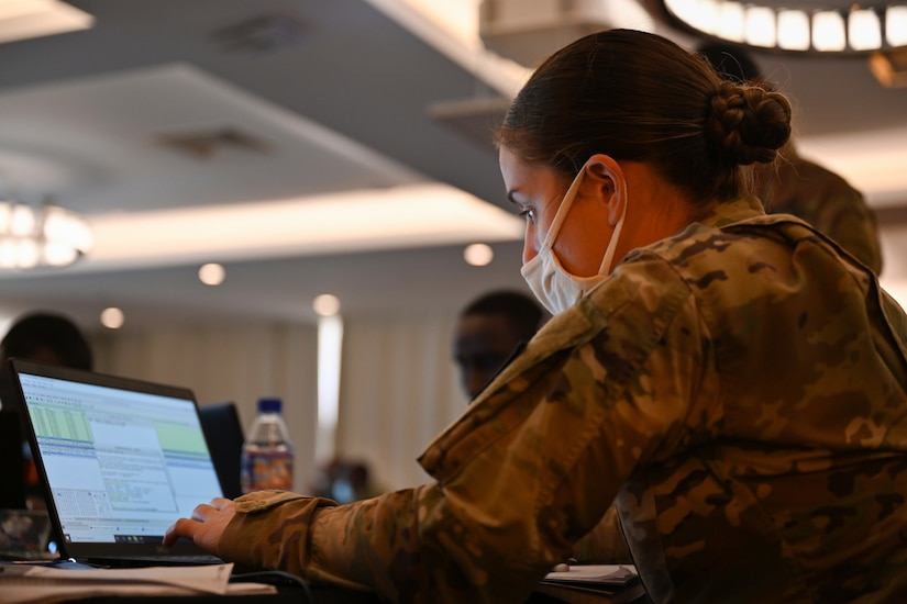 A woman in a military uniform types on a laptop.