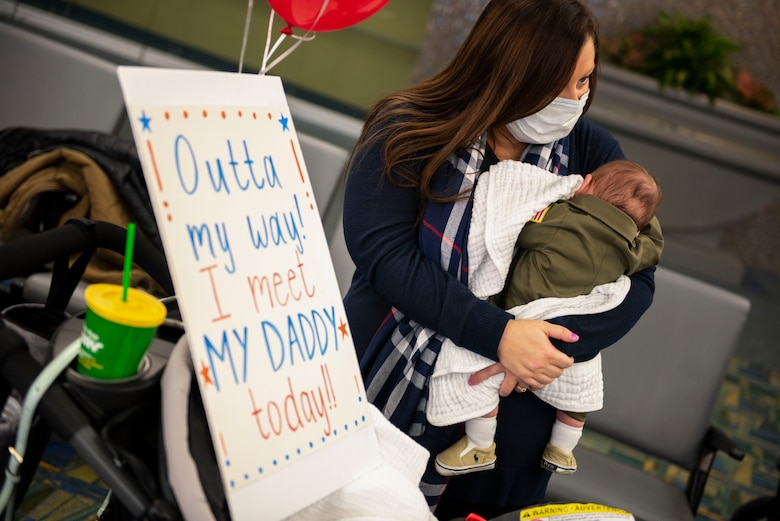 A mother and child await the return of their deployed Airman, assigned to the Ohio National Guard's 180th Fighter Wing, at the Eugene F. Kranz Toledo Express Airport, Dec. 31, 2020.