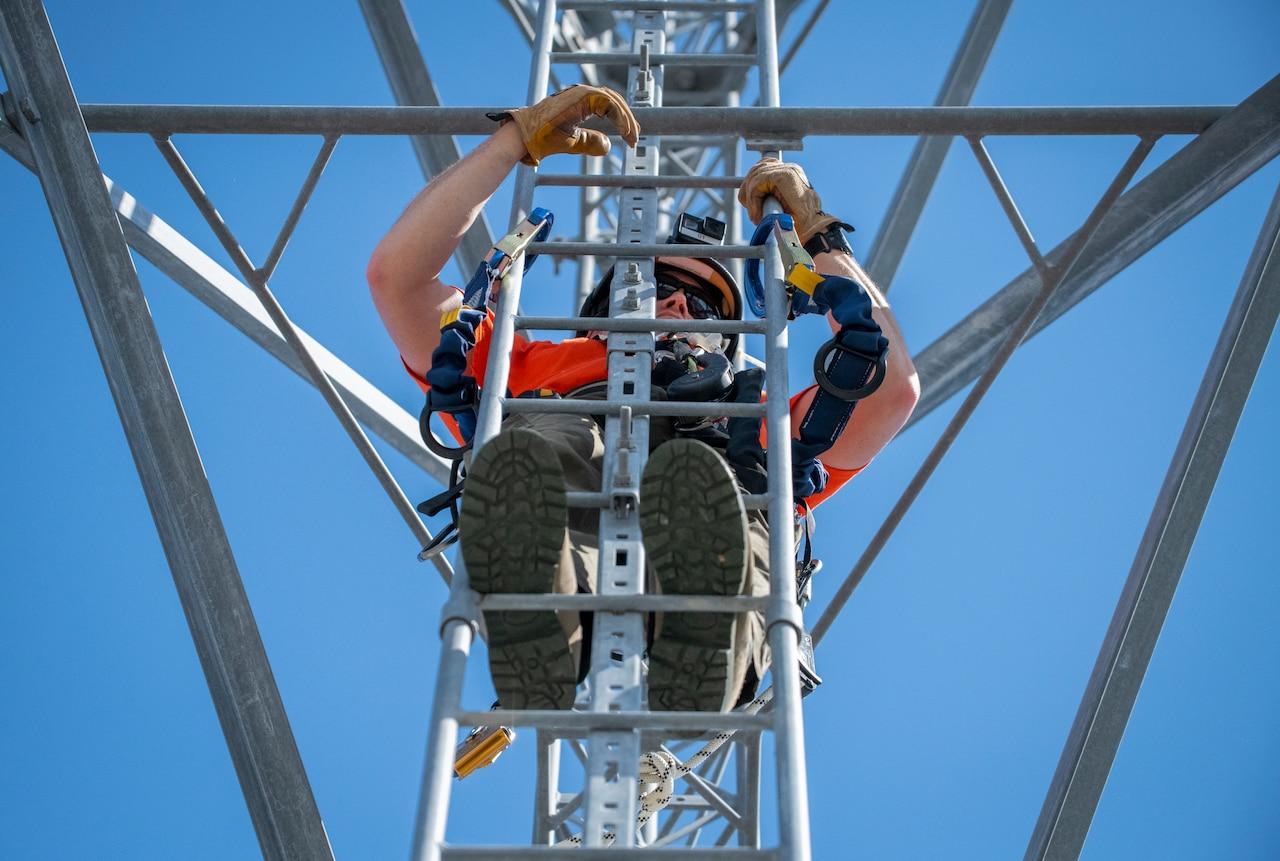 A man climbs a tower.