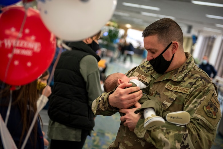 A U.S. Airman, assigned to the Ohio National Guard's 180th Fighter Wing, holds his child for the first time after returning home from an overseas deployment, Dec. 31, 2020 at the Eugene F. Kranz Toledo Express Airport.