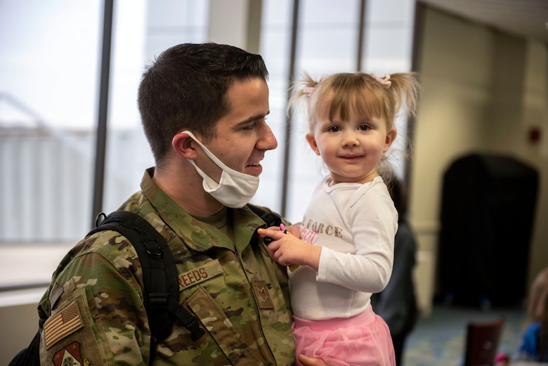 A U.S. Airman, assigned to the Ohio National Guard's 180th Fighter Wing, holds his child after returning from an overseas deployment, Dec. 31, 2020 at the Eugene F. Kranz Toledo Express Airport.