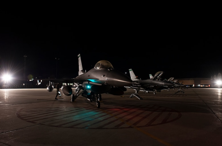 F-16 Fighting Falcon fighter jets, assigned to the Ohio National Guard's 180th Fighter Wing, sit ready on the flightline in the early morning hours, O.t. 12, 2020, before departing from the 180FW, in Swanton, Ohio, for an Aerospace Expeditionary Force deployment.