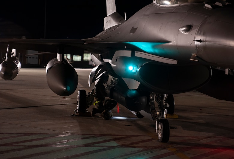 A U.S. Air Force Airman, assigned to the Ohio National Guard's 180th Fighter Wing, executes preflight procedures on an F-16 Fighting Falcon prior to an early morning launch, Oct. 12, 2020, as the fighter jets depart from the 180FW in Swanton, Ohio, for an Aerospace Expeditionary Force deployment.