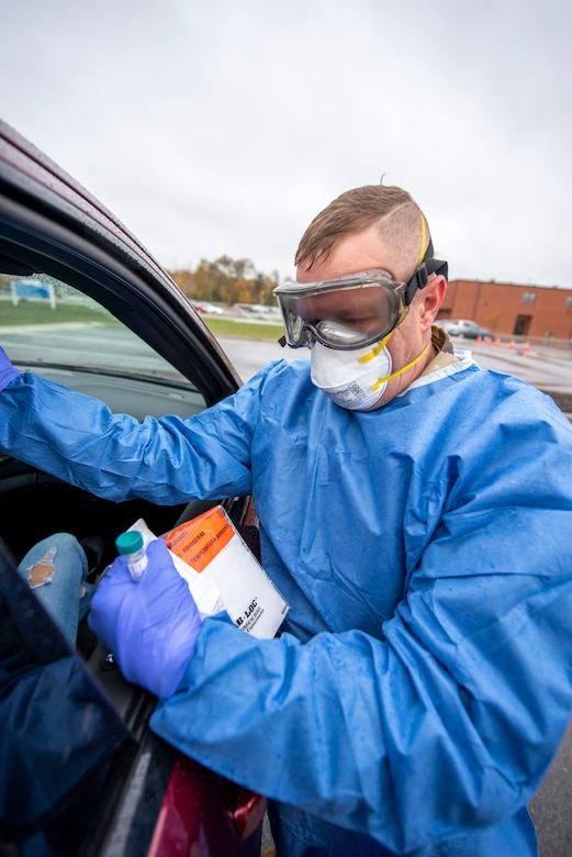 Cpl. Gene Meabon, a Soldier assigned to the Ohio Military Reserve, conducts a COVID-19 test during a pop-up testing drive-thru at Anthony Wayne Junior High School in Whitehouse, Ohio, Oct. 19, 2020.