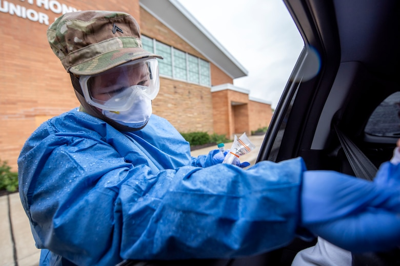 Cpl. Nikki Sherman, a Soldier assigned to the Ohio Military Reserve, conducts a COVID-19 test during a pop-up testing drive-thru at Anthony Wayne Junior High School in Whitehouse, Ohio, Oct. 19, 2020.