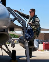 U.S. Air Force 1st Lt. T.J. Copic, an F-16 fighter pilot assigned to the Ohio National Guard's 180th Fighter Wing, climbs into the cockpit of an F-16 Fighting Falcon before a training flight at the 180FW in Swanton, Ohio, June 30, 2020.