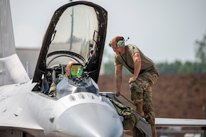U.S. Air Force Airman 1st Class Liam McDonald, a crew chief assigned to the Ohio National Guard's 180th Fighter Wing, prepares Capt. Joshua Caudill, an F-16 fighter pilot assigned to the 180FW, prepare for a training flight at the 180FW in Swanton, Ohio, Aug. 27, 2020.