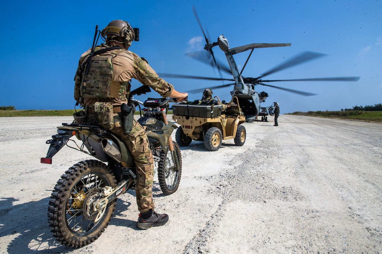 A service member sits on a motorcycle facing a helicopter.