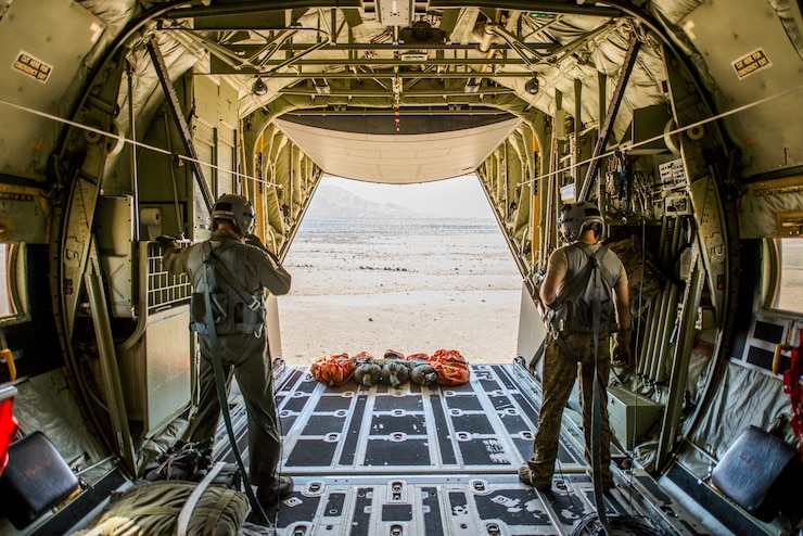Two Airman standing inside of a C-130. The back of the C-130 is open and you can see the desert and the airmen stand looking out at the desert.