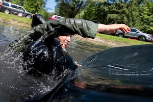 U.S. Air Force Capt. Jacob Laginess, an F-16 fighter pilot assigned to the Ohio National Guard's 180th Fighter Wing, flips a life raft over during water survival training in Waterville, Ohio, Aug. 8, 2020.