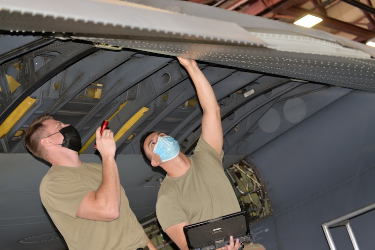 An Airman holds a flash light while another airman stands next to him and checks on the wing of an aircraft