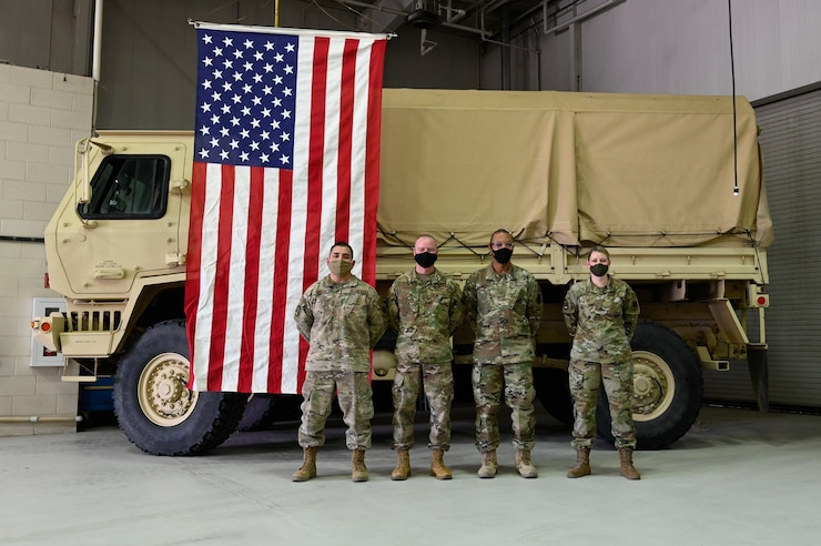 Four Airmen stand inside of a RED HORSE building and pose at parade rest as a group in front of a military vehicle and an American flag