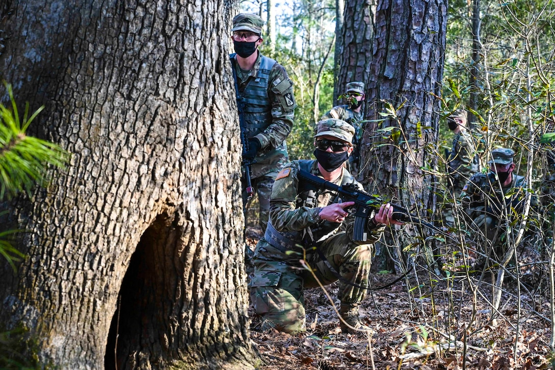 A soldier kneels behind a tree while holding a weapon; others stand behind.