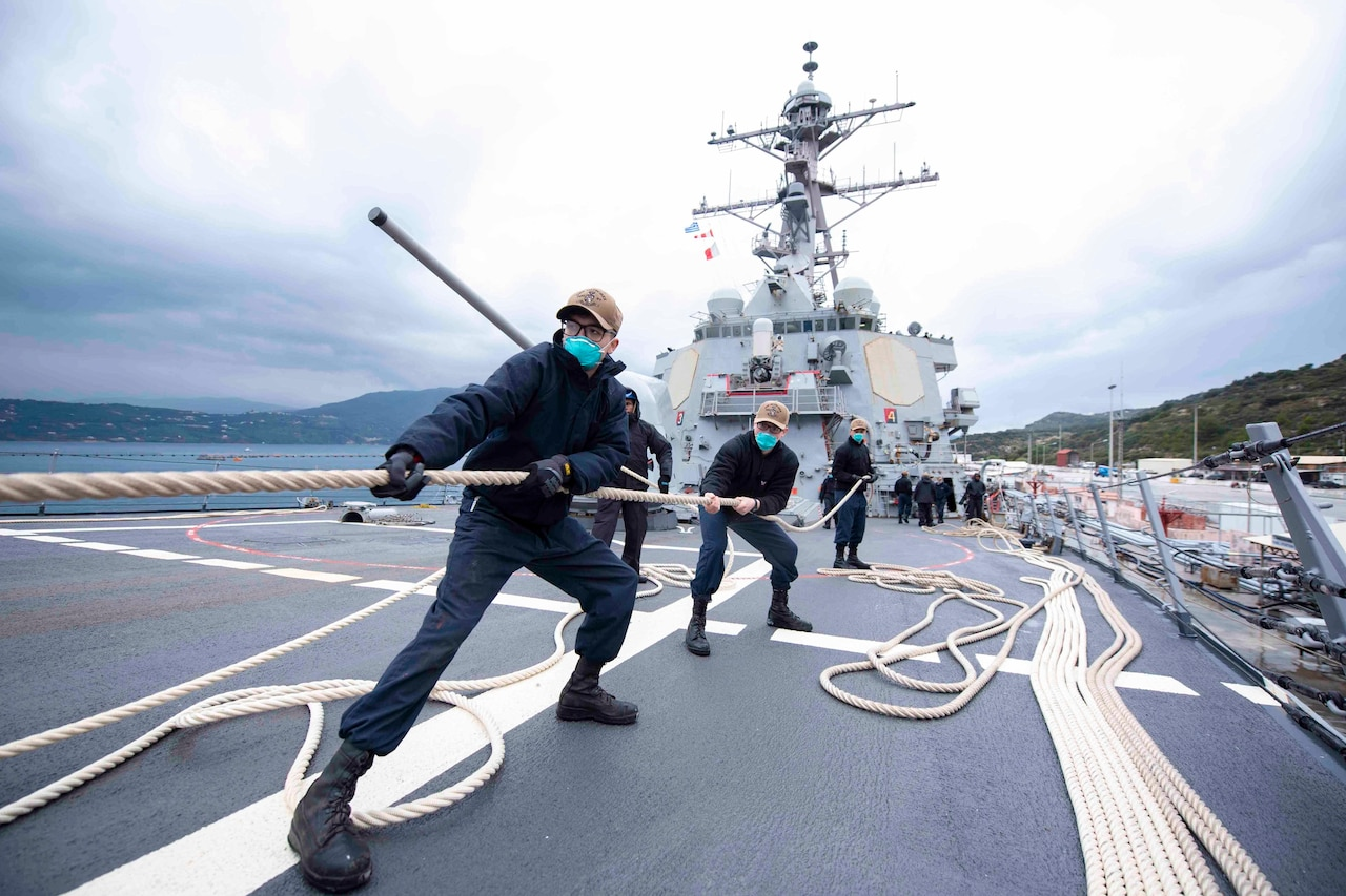 Sailors in a line pull a rope on the deck of a ship.