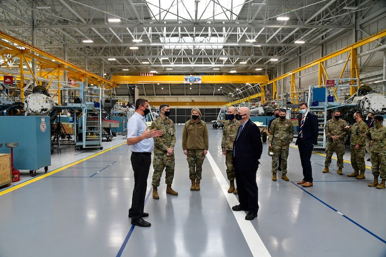Braeden Stander (front left), 573rd Aircraft Maintenance Squadron director, briefs Acting Secretary of the Air Force John Roth (front right), and other leaders.