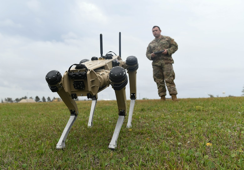 A uniformed Airman is controlling a robot dog by it's controller