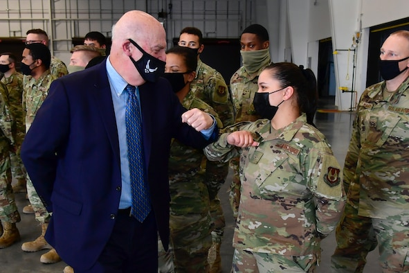 Acting Secretary of the Air Force John Roth exchanges an elbow bumps with Airman Alexis Shook, 649th Munitions Squadron.