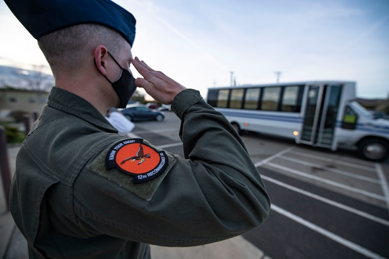 An airman from the 12th Reconnaissance Squadron (RS) salutes the bus carrying Chief Master Sgt. of the Air Force JoAnne Bass as it arrives at a dining facility on Beale Air Force Base.