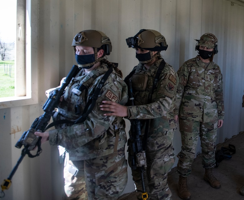 Chief Master Sgt. of the Air Force JoAnne Bass, right, watches as two airmen with the 9th Security Forces Squadron's (SFS) tactical response team run through a building clearing demonstration on Beale Air Force Base