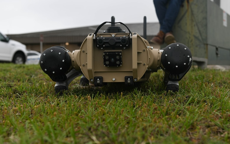 A robot dogs lays flat on the ground.