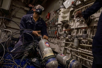 Damage Controlman 3rd Class Pierre Lapierre maintains self-contained breathing apparatus tanks aboard USS Makin Island (LHD 8).