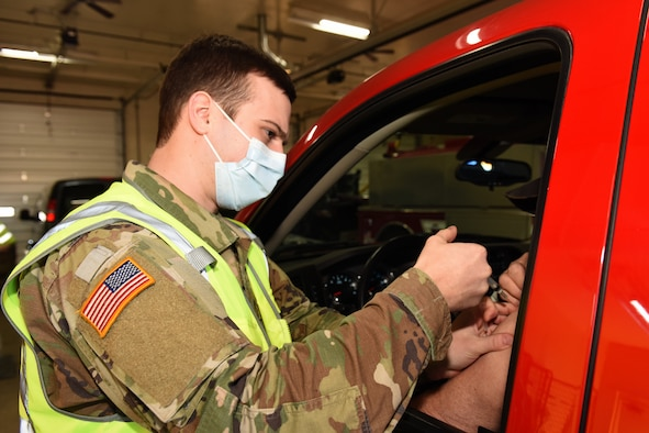 A Michigan Army National Guard Soldier with the Task Force North COVID-19 Vaccination/Testing Team (CVTT) vaccinates members of the community at the Grayling Fire Department, Grayling, Michigan, March 13, 2021. Guard members are helping local health officials get Michiganders vaccinated.