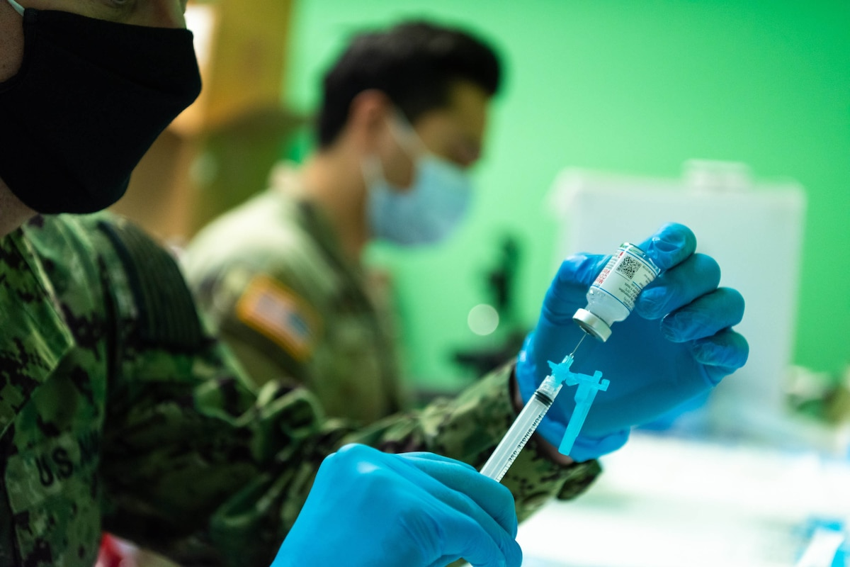 A service member puts vaccine into a syringe.